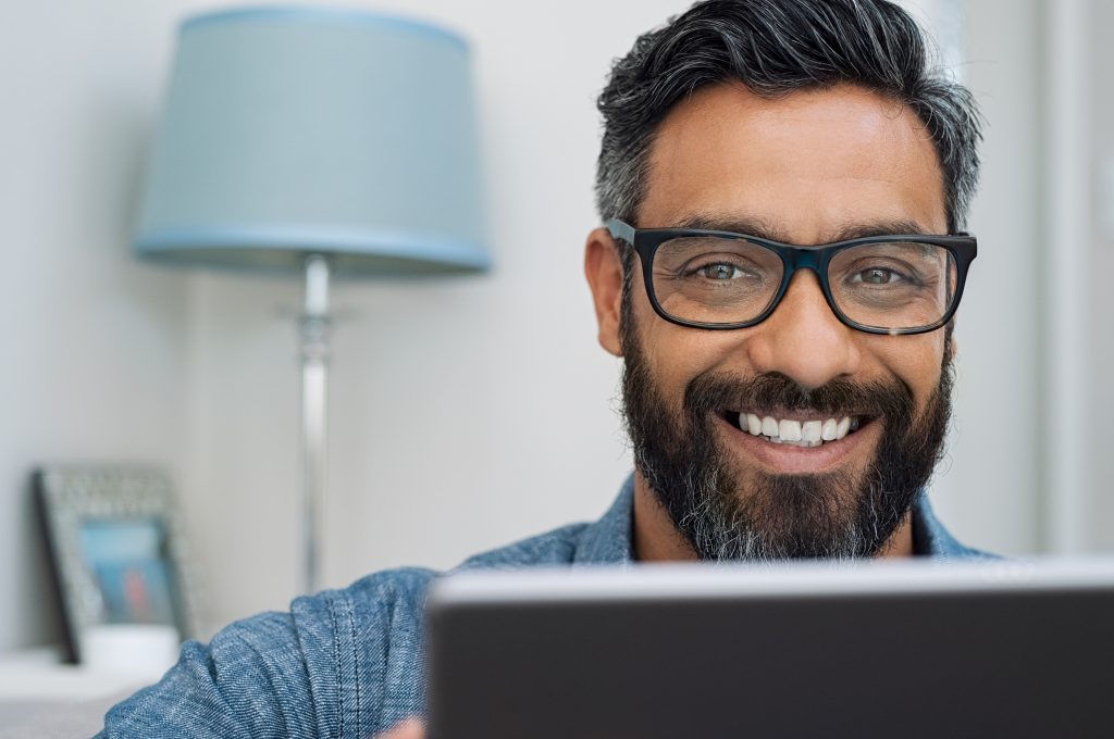 Closeup of businessman wearing glasses and working on laptop